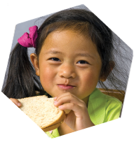 Smiling girl eating a peanut butter sandwich